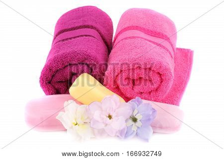 Towels soaps and flowers isolated on white background.