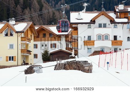ORTISEI, ITALY. March 28, 2016: Ski lift gondola in Ortisei, Northern Italy. Ski run. Houses along the snowy path. Ski resort of Ortisei, Italy.