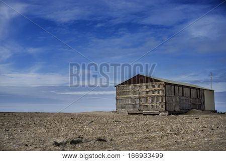Desert landscape, lonely abandoned house on the sand.