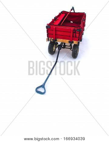 Red wood wagon with red bag and a red sky stick. Black wheels blue handle and the wagon shadow over snow.