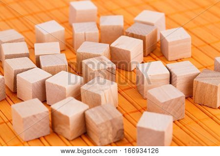 Many wooden cubes on a bamboo background.