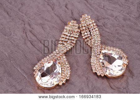 Stylish earrings with stones on fabric background.