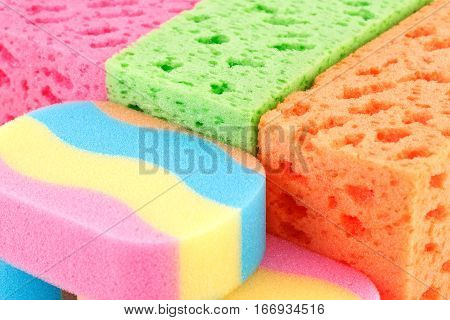 Many colorful sponges horizontal close up picture.