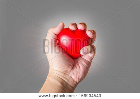 close up hand hold heart symbol on flare light background