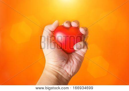 close up hand hold heart symbol on orange background
