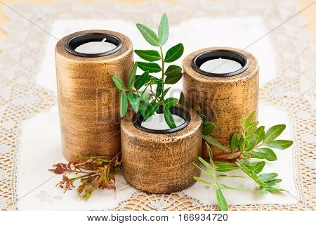 Three brown ancient style candle nests and green leaves on cloth background.