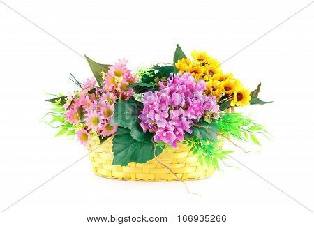 Colorful fabric flowers in wicker basket isolated on white background.