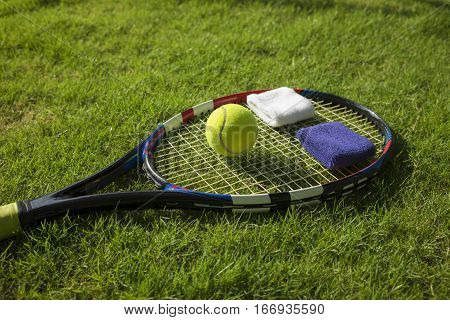 Tennis Ball, Racket And Wristbands On Grass Field Ground Under Sunlight