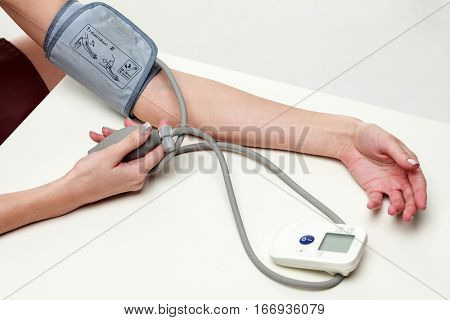 Woman measures her blood pressure, isolated on white background