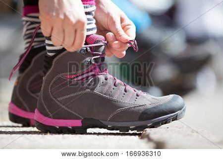 Starting ready concept. A woman is tying the hiking shoes. She is about to start a sports day dedicated to physical activity. Movement, sports, activities and competition concept.
