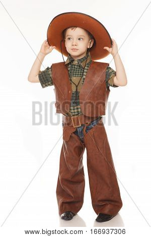 Little happy boy in cowboy costume on the white background