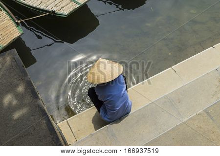 Vietnamese woman washing on river side. Concept of difficult life of Asian woman