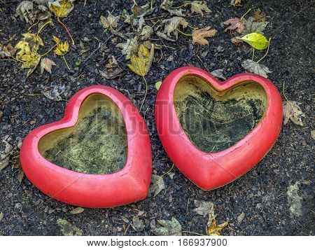Two red heart-shaped flowerpots placed in the garden