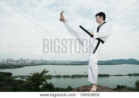 one asian man playing with taekwondo outdoor