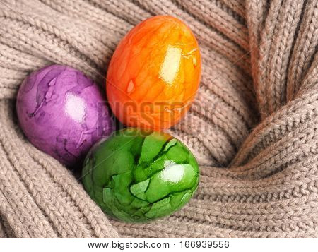 Three colored Easter eggs in a scraf Easter holiday background