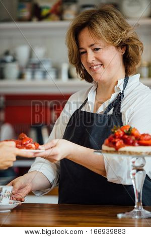 Portrait of adult smiling confectioner serving customer with strawberry cake and drink