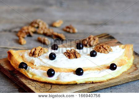 Delicious ruddy omelette with soft cottage cheese, walnuts and berries on a wooden board. Sweet berry breakfast omelette. Kids cooking recipe. Rustic style. Closeup