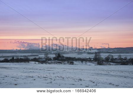 Working Nitrogen Plant in smoke on the background of dawn in winter. Abandoned village in the foreground. Grodno, Belarus.