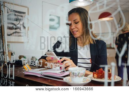 Portrait of beautiful smiling brunette chatting over cell in cafe at table with cake and drink
