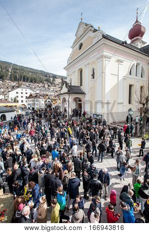 ORTISEI, ITALY. March 27, 2016: Church and crowd of faithful. Easter in Ortisei, Italy. Many faithful gathered outside the church in Ortisei in Val Gardena in northern Italy. Easter Day festivities.