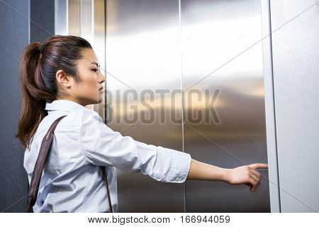 Businesswoman pressing elevator button in office
