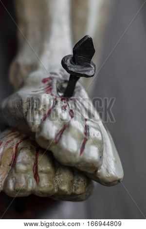 Closeup of feet of Jesus Christ nailed to the cross during the crucifixion. Shallow depth of field. Defocused blurry background.