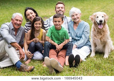 Portrait of cheerful extended family sitting in the park