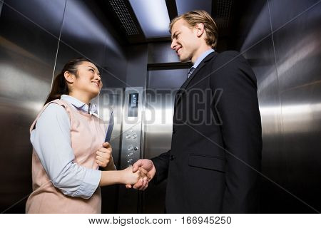 Businessman smiling and shaking hands with businesswoman in elevator