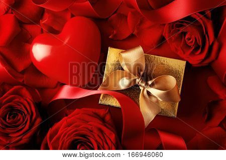 gift box, red heart, ribbon and rose petals on red background. Valentine's Day decoration
