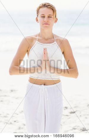 Beautiful woman in lotus position on the beach