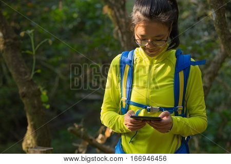 closeup of young woman reading ebook on park