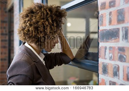 Tired businesswoman leaning on window in office
