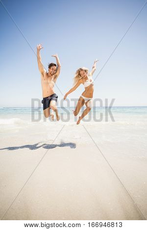 Happy couple jumping on the beach with arms outstretch
