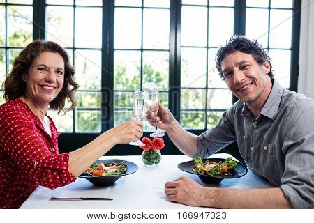 Middle-aged couple toasting champagne flutes while having lunch in a restaurant