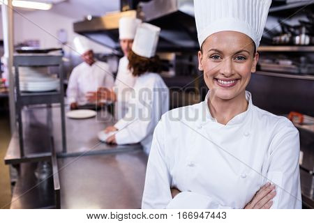 Happy chef standing in commercial kitchen and three chefs discussing In background