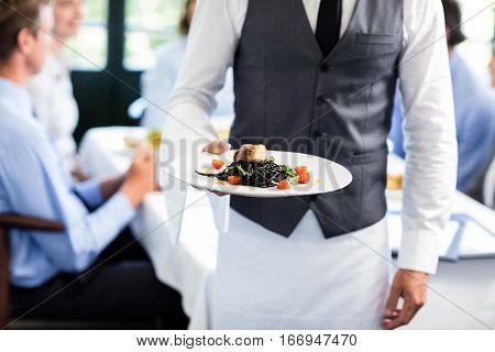 Close-up of waiter holding plate of meal in restaurant