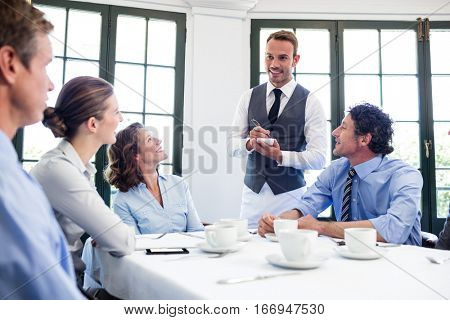 Waiter taking an order from business people in restaurant