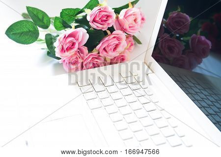 Laptop computer with pink rose bouquet in background. Technology and love concept
