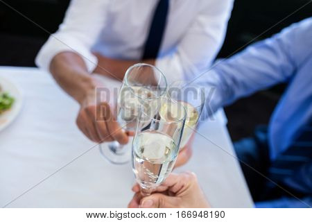Close-up of hands toasting champagne flutes