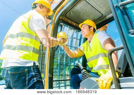 Two Asian workers in protective vests standing on construction machinery on building site