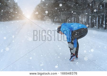 Woman Running Clutching Calf Muscle Injury After Spraining It While Out Jogging On The Snowy Road. F