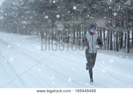 Female Running Sprinting Up A Snowy Road During A Winter Training Run.