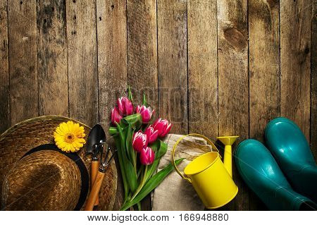 Gardening tools flowers watering can rubber boots and straw hat on vintage wooden table. Spring summer or garden concept background with free text space.