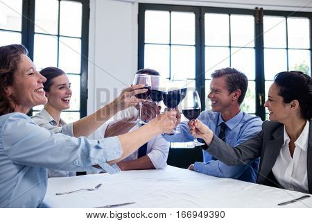 Group of businesspeople toasting wine glass during business lunch meeting in a restaurant