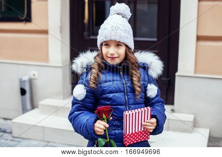 Child girl in jacket and cap with a flower and a book. Concept of holiday birthday Valentine's Day