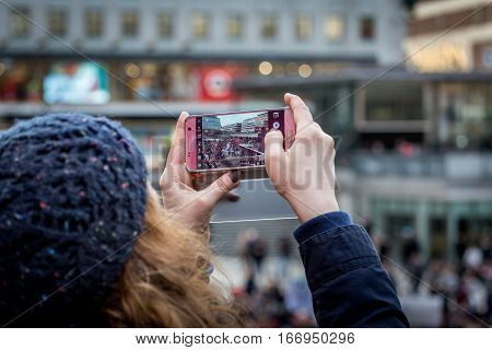 Anti-Trump day demonstration. Stockholm, Sweden - January 21, 2017: Woman taking picture on crowd of people and speaker during demonstration January 21, 2017. Close up of hands holding mobil phone.