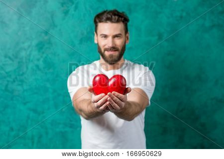 Handsome man in the white t-shirt giving red heart standing on the painted green wall background. image focused on the hands with heart. Valentine's Day concept
