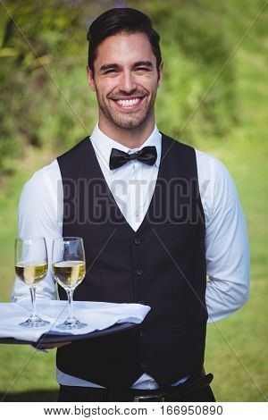 Handsome waiter holding a tray with two glasses of wine outside
