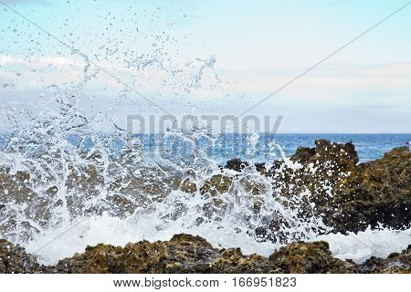 waves breaking over rocks causing small droplets breaking up in the sky early in the morning