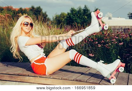 Portrait of a beautiful young blonde girl tighten the laces sitting on a bench in a vintage roller skates, wearing shorts, golfs and a T-shirt. Hot summer day. Outdoor.